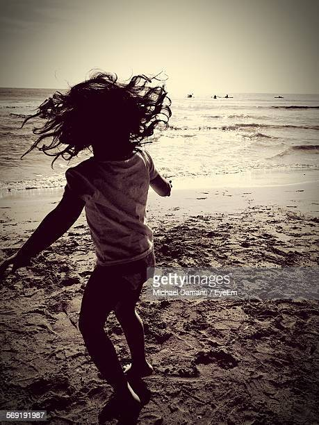 rear view of girl with tousled hair against sky on beach - michael damanti fotografías e imágenes de stock