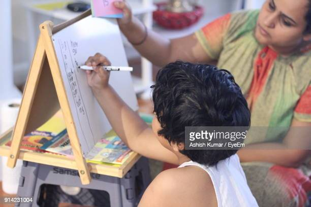 Rear View Of Girl Writing On Board