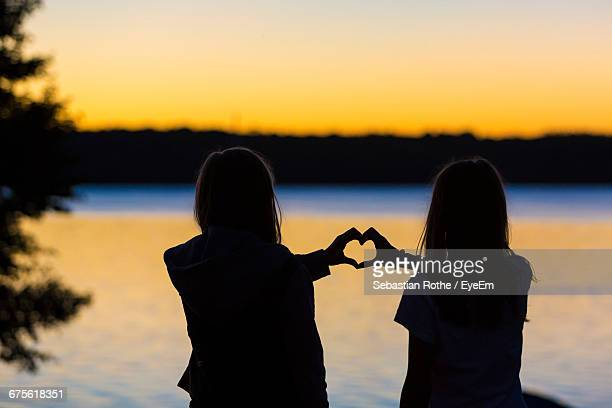 Rear View Of Girls Forming Heart Shape With Hands Against Lake During Sunset