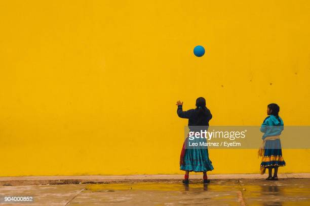 Rear View Of Girls Playing With Ball Against Yellow Wall