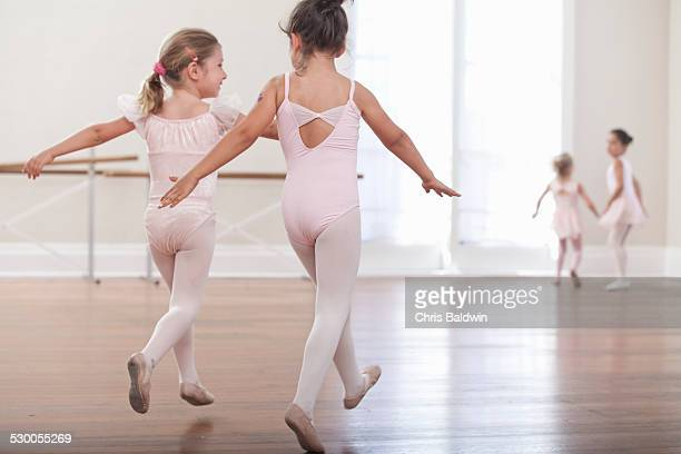 Rear view of girls practicing jump in ballet school