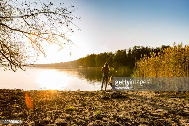 rear view of girls relaxing at lakeshore against sky during sunset - seeufer stock-fotos und bilder