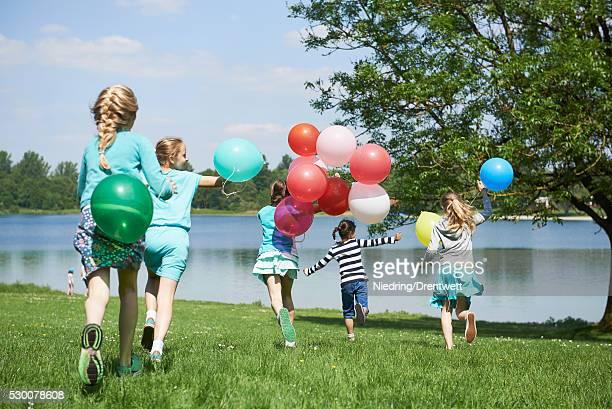 Rear view of girls running in park with balloons, Lake Karlsfeld, Munich, Bavaria, Germany
