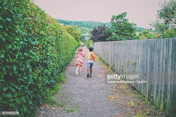 Rear View Of Girls Running On Footpath