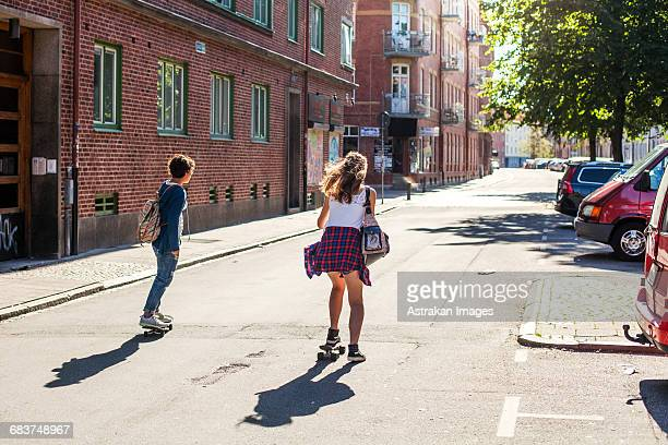 rear view of girls skateboarding on street by buildings - malmo stock pictures, royalty-free photos & images