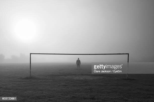 rear view of goalie standing against goal post on field in foggy weather - defender soccer player stock photos and pictures