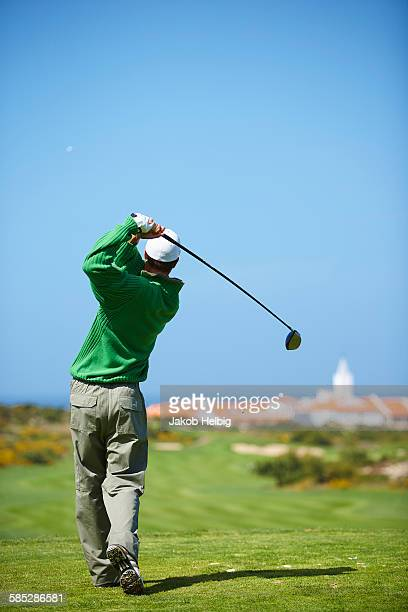 Rear view of golfer holding golf club taking golf swing