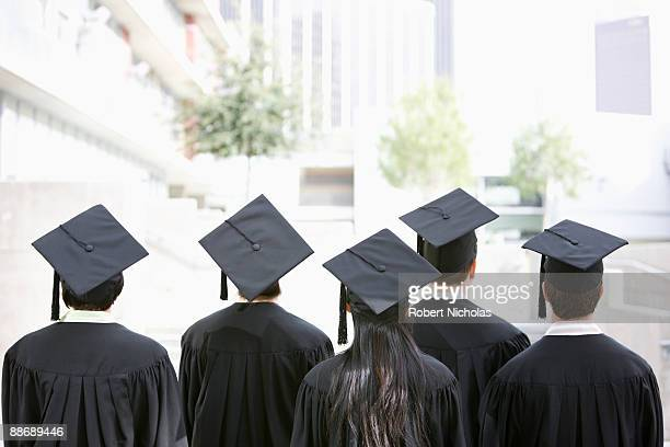 rear view of graduates in caps and gowns - graduation cap stock pictures, royalty-free photos & images