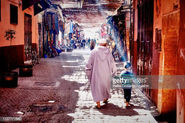 rear view of grandfather and boy walking on street in town - マラケシュ ストックフォトと画像