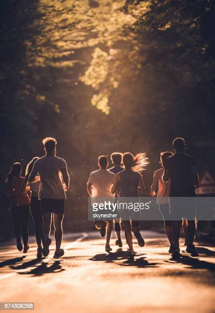 Rear view of group of athletes running a marathon at sunset.
