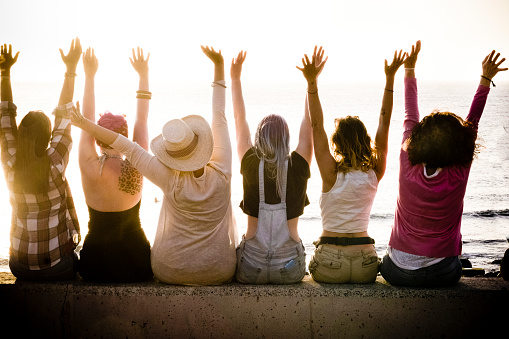 rear view of group of females caucasian friends enjoying at the sunset with ocean in background - success and satisfaction concept for nice people together with joy - friendship and vacation 1131620452