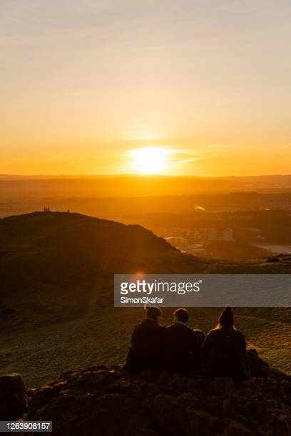 rear view of group of friends looking at sunrise over mountain landscape, edinburgh uk - sunrise dawn stock pictures, royalty-free photos & images
