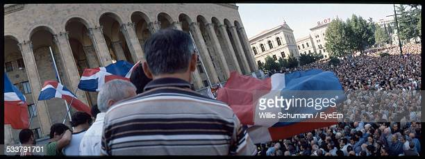 rear view of group of men with flags at elevation, looking at crowd standing near government building - dominican republic flag stock pictures, royalty-free photos & images