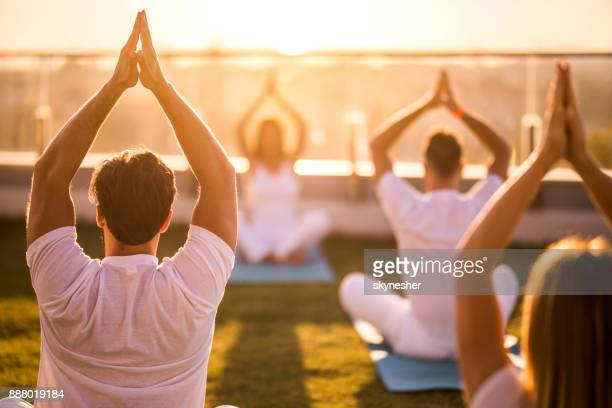 Rear view of group of people doing Yoga meditation exercises on a terrace.