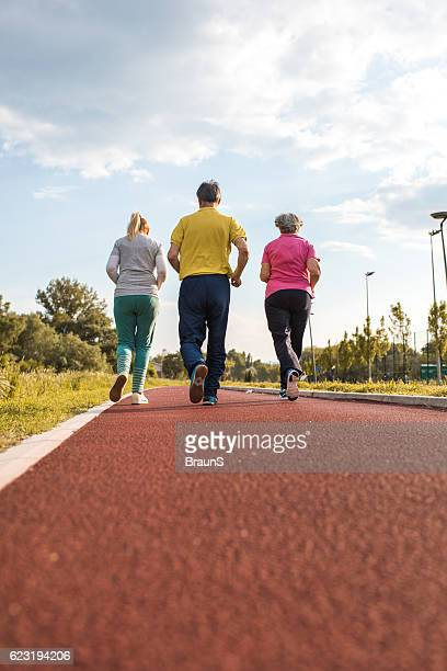Rear view of group of people jogging on running track.