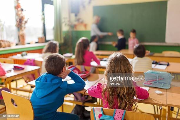 rear view of group of school children attending a class. - bijwonen stockfoto's en -beelden