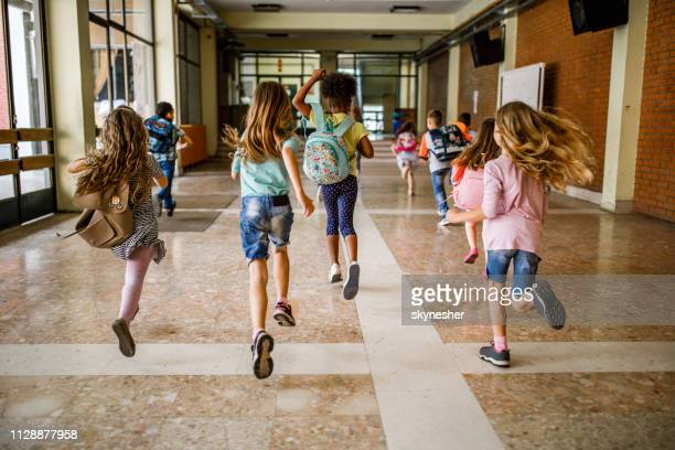 rear view of group of school children running down the hallway. - finishing stock pictures, royalty-free photos & images
