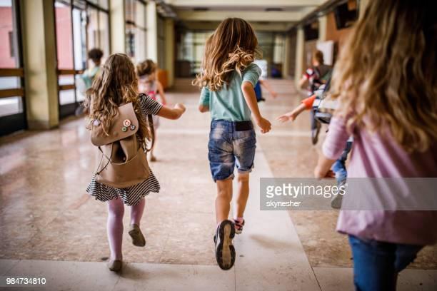 vista traseira do grupo de crianças correndo pelo corredor. - criança de escola - fotografias e filmes do acervo
