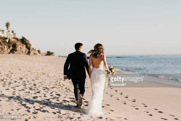 rear view of happy bridal couple running at the beach - bride stock pictures, royalty-free photos & images