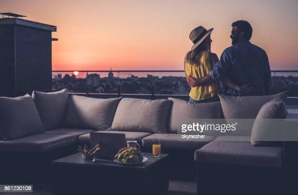 Rückansicht des glücklichen Paares Kommunikation auf einem Penthouse Balkon bei Sonnenaufgang.