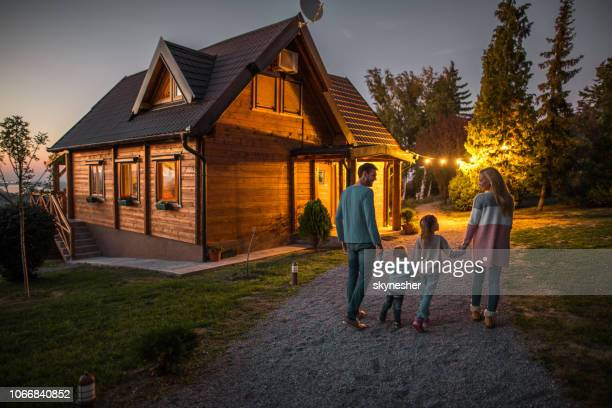 rear view of happy family holding hands and walking by their chalet in the evening. - house stock pictures, royalty-free photos & images