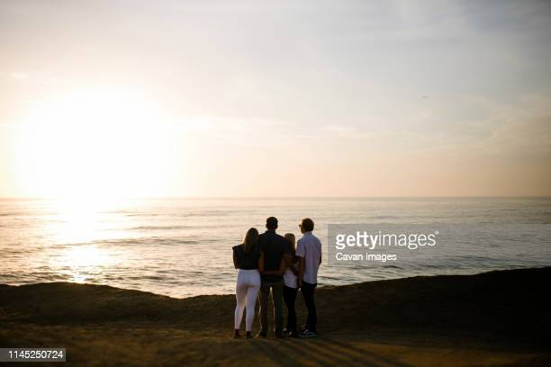 rear view of happy family looking at sea while standing on cliff against sky during sunset - four people stock pictures, royalty-free photos & images