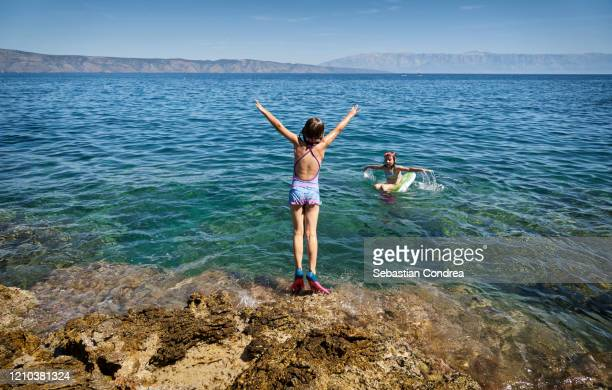 rear view of happy kids at the beach with hands raised jumping in the sea, jelsa island of croatia. - croatia stock pictures, royalty-free photos & images