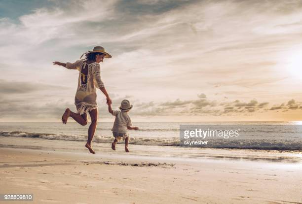 rear view of happy mother and son holding hands while jumping on the beach. - bambini in spiaggia senza costume foto e immagini stock