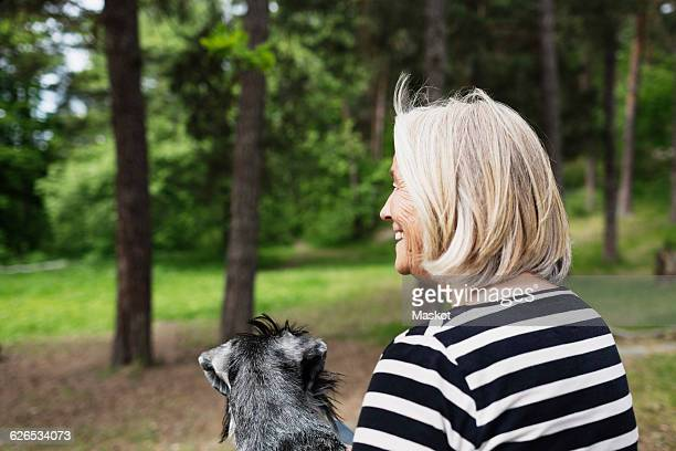 Rear view of happy senior woman sitting with dog at field