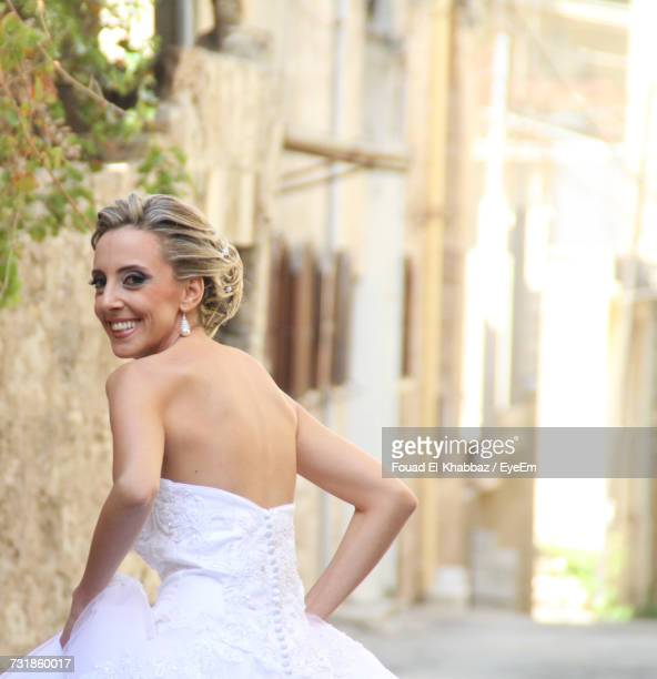 Rear View Of Happy Woman Wearing Wedding Dress On Street