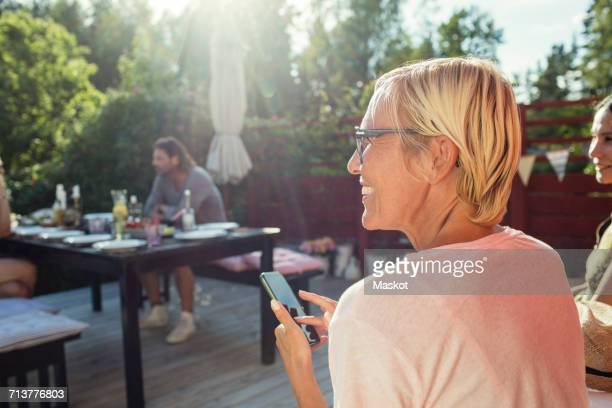 rear view of happy woman with mobile phone in back yard on sunny day - looking away stock pictures, royalty-free photos & images