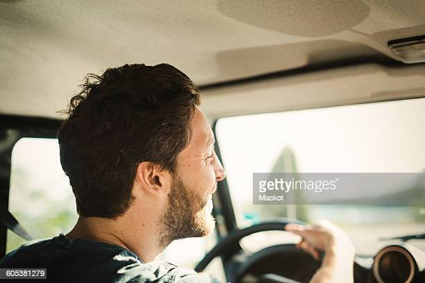 Rear view of happy wonderlust man driving car
