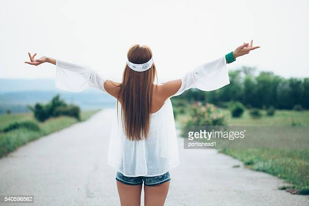 rear view of happy young woman standing on the road - rear end stock photos and pictures