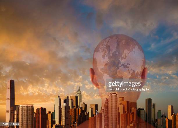 Rear view of head of person with globe near city skyline