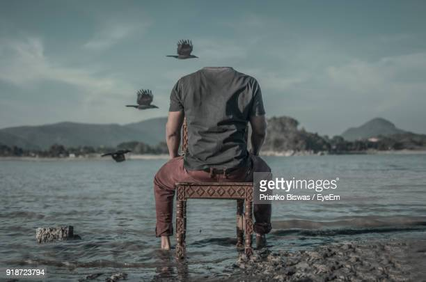 Rear View Of Headless Man Sitting On Chair At Lakeshore Against Sky