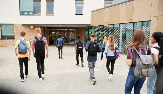 Rear View Of High School Students Walking Into College Building Together 1047528856