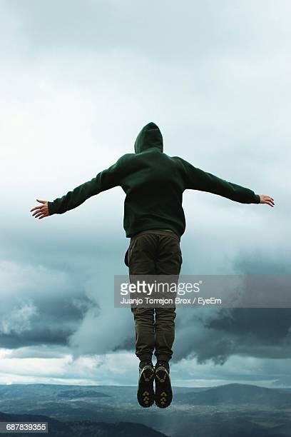 Rear View Of Hiker In Mid-Air Against Cloudy Sky
