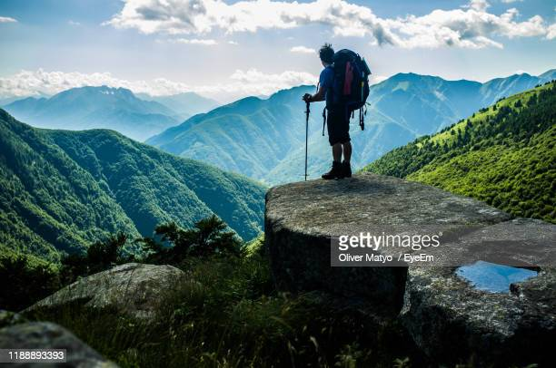 rear view of hiker looking at mountains against sky - ticino canton stock pictures, royalty-free photos & images