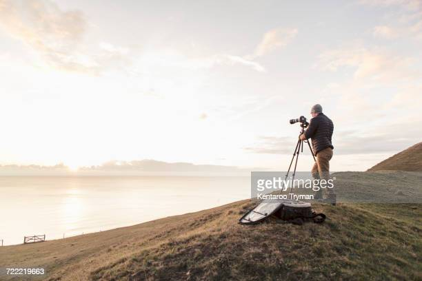 Rear view of hiker photographing sea through SLR camera while standing on hill
