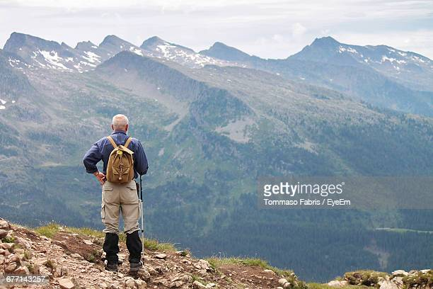 Rear View Of Hiker Standing On Mountain