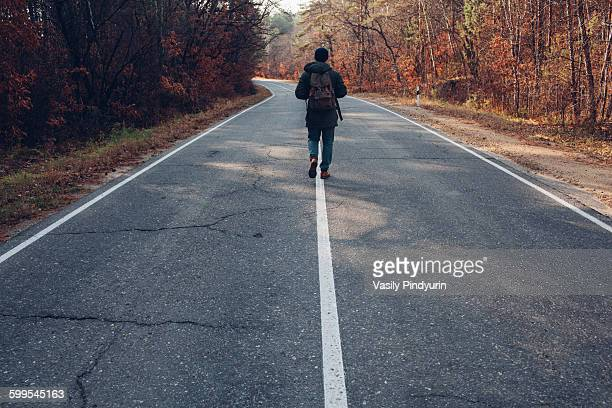 Rear view of hiker walking on country road