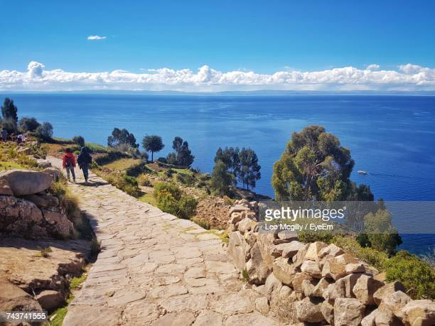 rear view of hiker walking on footpath by lake titicaca against blue sky during sunny day - lago titicaca fotografías e imágenes de stock