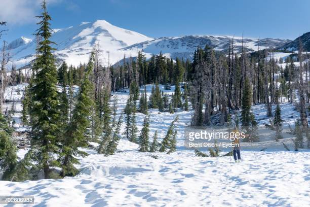 Rear View Of Hiker Walking On Snow Covered Field At Mount Adams