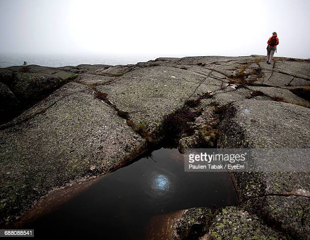rear view of hiker walking rock against clear sky - paulien tabak stock pictures, royalty-free photos & images