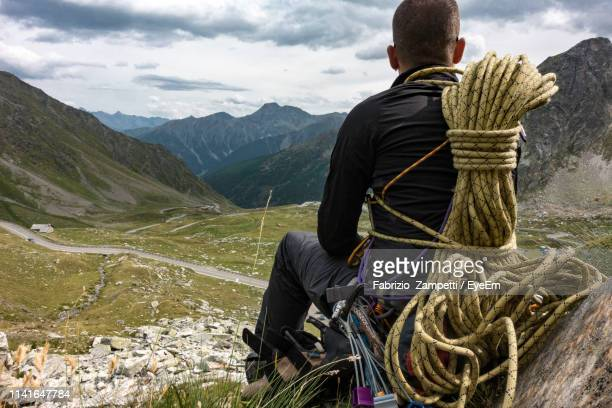 rear view of hiker with rope sitting on field against mountain range - fabrizio zampetti foto e immagini stock