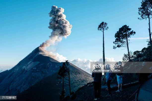 Rear View Of Hikers Looking At Acatenango Volcano Against Blue Sky