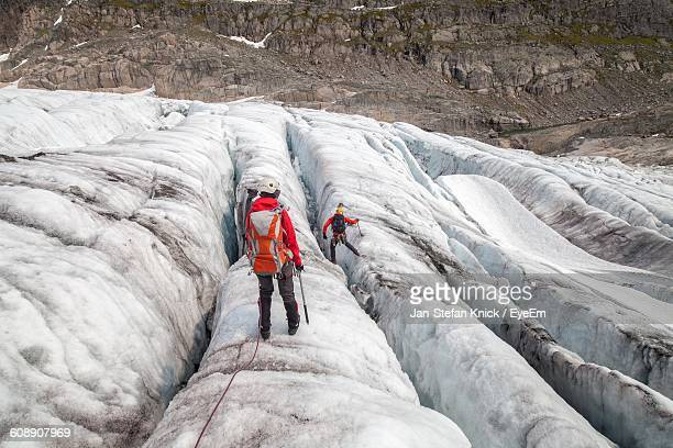 rear view of hikers on glacier against rocky mountains - crevasse stock photos and pictures