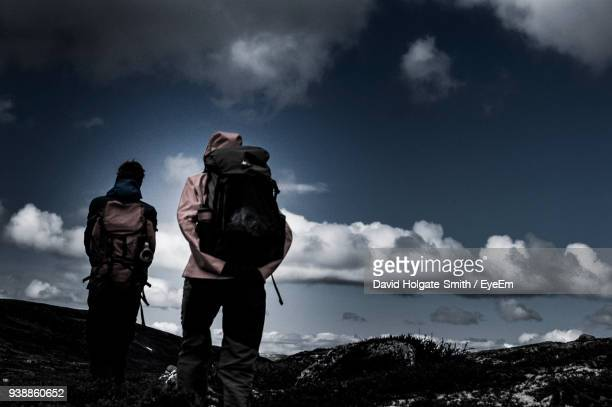Rear View Of Hikers On Mountain Against Sky