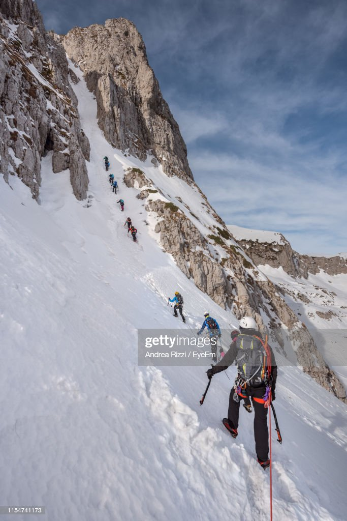Rear View Of Hikers On Snow Capped Mountain : Foto stock