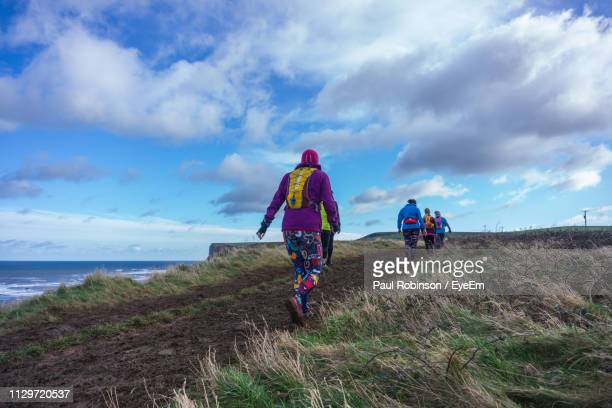 rear view of hikers walking on cliff against sky - cleveland stock pictures, royalty-free photos & images